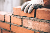 Fototapety Close up of industrial bricklayer installing bricks on construction site