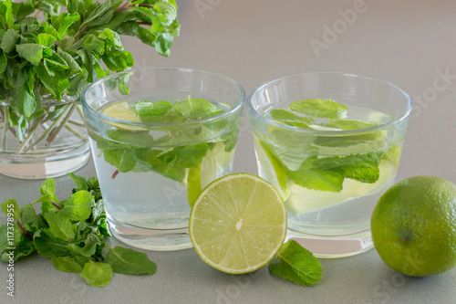 Fototapeta Mojito cocktail with lime and mint in glass on a grey background