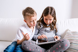 Children at home sitting on sofa, playing with tablet