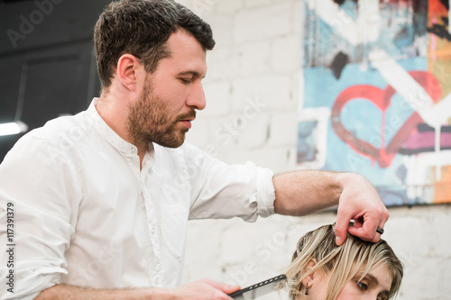 Male hairdresser making haircut for a client in professional hairdressing salon Slika na platnu