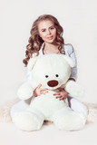 Pretty dark blonde girl wearing in wight clothes hugging teddy bear on white background. Image released. Isolated.