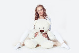 Tender blonde girl wearing in wight clothes hugging teddy bear on brick wall background. Girl with brown eyes looking at the camera image released.