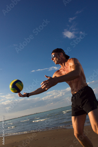 Fototapeta Beach volleyball. The player makes the pitch.