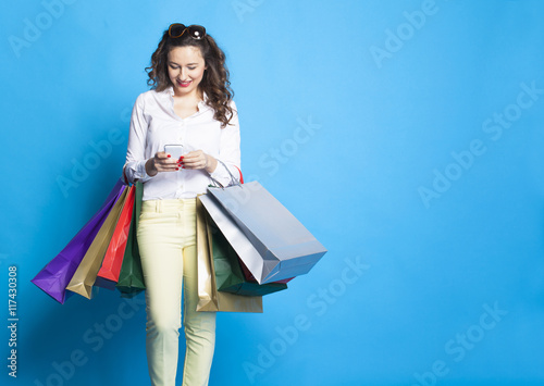 Girl with shopping bags on blue background.