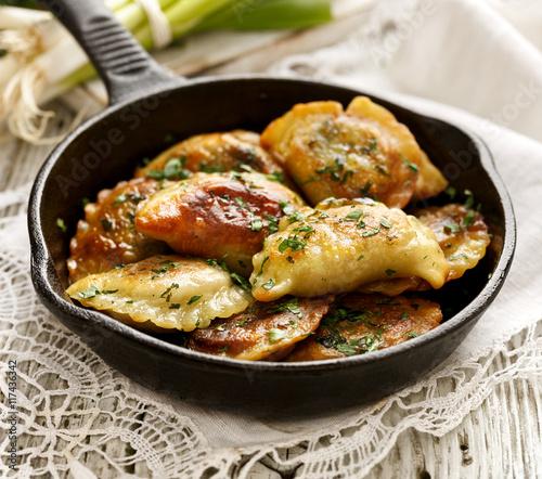Fototapeta Baked dumplings on a cast-iron frying pan