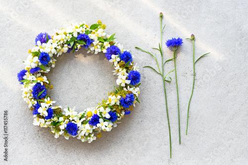 Leinwanddruck Bild Bluet floral wreath on concrete background.