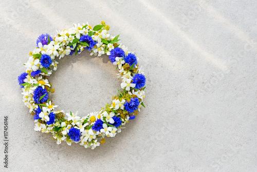 Leinwanddruck Bild Floral wreath on concrete background.