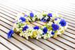 Leinwanddruck Bild - Floral wreath on wooden table.