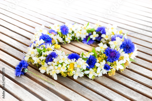 Leinwanddruck Bild Floral wreath on wooden table.