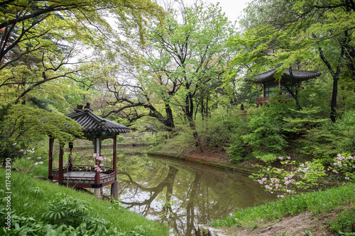 Scenic view of a pond, lush nature and two pavilions at Huwon (Secret Garden) at the Changdeokgung Palace in Seoul, South Korea.