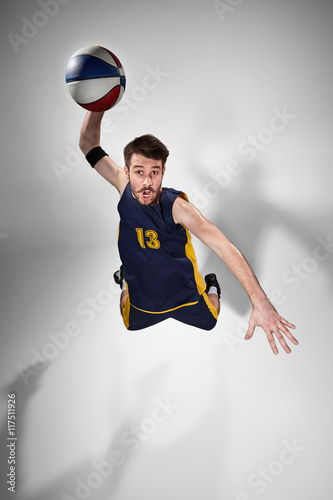 Fototapeta Full length portrait of a basketball player with ball