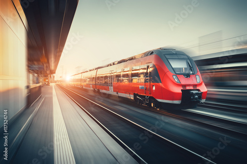 Fototapeta Beautiful railway station with modern red commuter train at suns