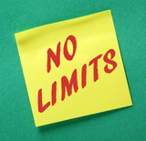 The words No Limits on a yellow sticky note posted on a green notice board as a reminder that you van succeed against the odds