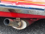 Verchromte Stoßstange eines orangeroten alten englischen Roadsters mit Sportauspuff in Wettenberg