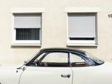 Klassisches Coupé der Fünfziger und Sechziger Jahre in Beige mit schwarzem Dach vor Zwillingsfenstern mit Rollladen in Wettenberg bei Gießen in Hessen
