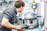 metal machining industry. Worker operating cnc milling machine