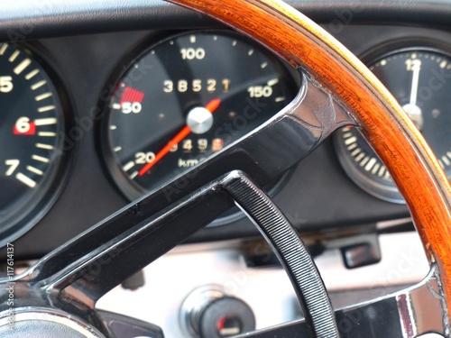 Holzlenkrad und klassische Rundinstrumente eines deutschen Sportwagen der Sechzi Poster