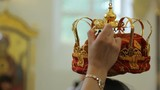 Person keeps massive golden crown in right hand in church.