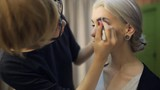 Chinese woman does make-up to model sitting in dressing room.
