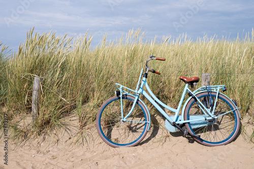 Niebieski rower zaparkowany na holenderskich wydmach