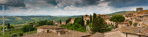 Fototapeta Over the rooftops of San Giminano. Panoramic view from the medieval town with part of the city and a tuscan landscape on a stormy day.