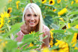 Hübsche blonde Frau mittleren Alters im Sonnenblumenfeld