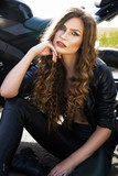 Sexual biker woman wearing black leather jacket with her sport motorcycle on a highway. Beauty, fashion. Adventure and freedom.