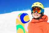 portrait of a snowboarder smiling on the top of the mountains