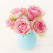pink rose flowers in a vase on white wooden background. shabby chic colors