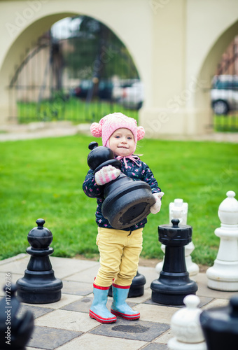 Poster little girl taking a chessman