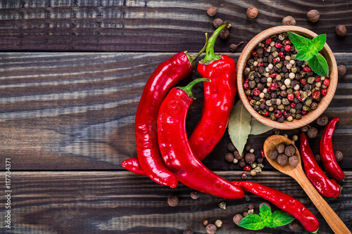 Fototapeta Powder spices on spoons in black wooden table background
