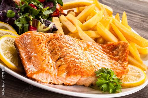 Fototapeta Fried salmon, chips and vegetables