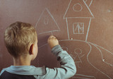 little boy draws with chalk on a blackboard,