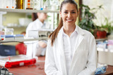 Young female  scientist  standing in her lab. - 117741118