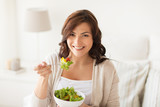 smiling young woman eating salad at home