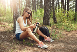 Female backpacker resting with cup of tea during hike in the countryside. Concept of lifestyle and adventure.