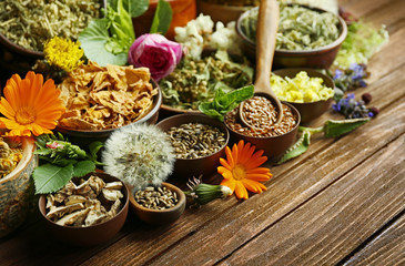 Herb selection and fresh flowers in bowls on wooden background