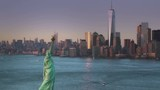 Aerial footage of New York City with Statue of Liberty, filmed at sunset. - 117767101