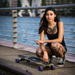 attraktive tätowierte junge Frau mit Longboard