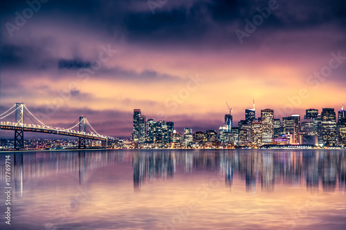 Poster San Francisco California skyline with lights and bay under colorful sunset sky