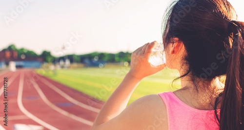 Female athlete drinking water on a running track
