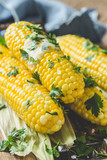 Homemade boiled corn on cob with butter and salt on rustic table