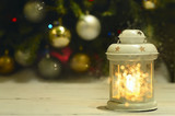 Christmas candle in the shape of a lantern with a candle inside. beautiful light coming and a lot of gold bokeh circles. In the background is blurred image Christmas tree decorated with toys. 
