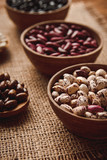 Beautiful multi-colored beans in ceramic bowls on a background of burlap