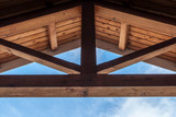 Wooden beam ceiling with symmetrical design. Modern art and design. Interior design with wood detail. Abstract minimal art. Blue sky background. Artistic design. geometrical balance and design. - 117830511