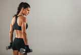 Strong muscular young woman holding dumbbells