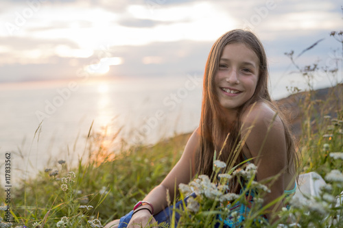 Poster Teenager girl at sunset on the side of the sea