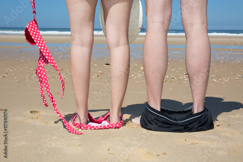 Naked couple standing on the beach with their swimmwear on their feet Poster