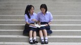 Cute Asian Thai high schoolgirls student couple in school uniform sit on the stairway discussing and reading homework or exam together.