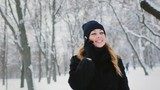 Young attractive woman talking on the phone in a winter park, smiling